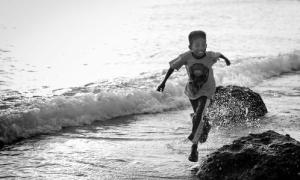 Child running at Pantai Kilo Lima by Travis Longmore Photography